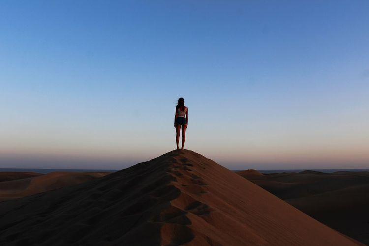 Full length of woman standing on sand dune against sky during sunset