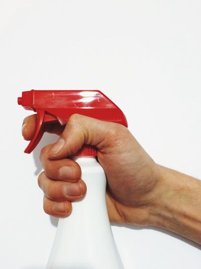 Cropped image of man holding spray bottle over white background