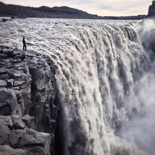 Man standing at the edge of dettifoss against sky