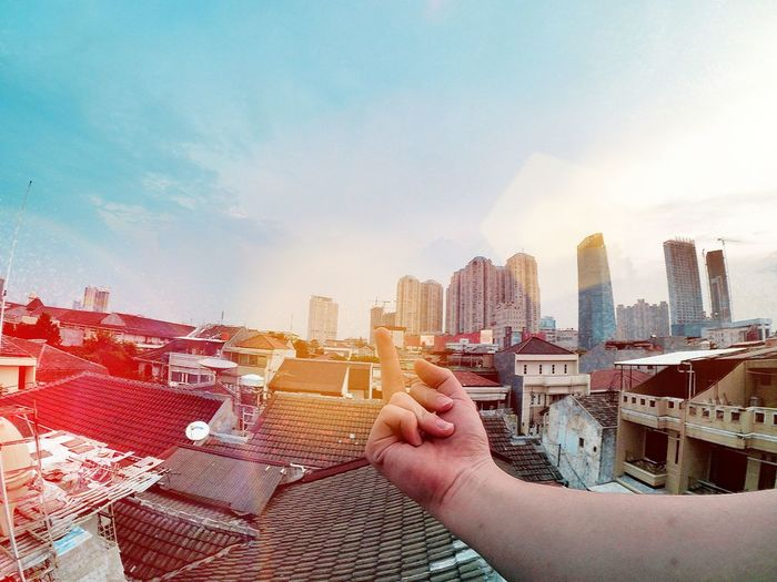 Cropped hand showing middle finger against sky in cityscape