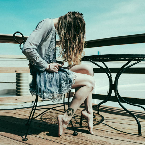 Full length of woman sitting on chair against sky