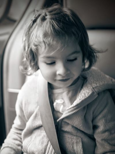 Close-up of girl looking down while sitting in car