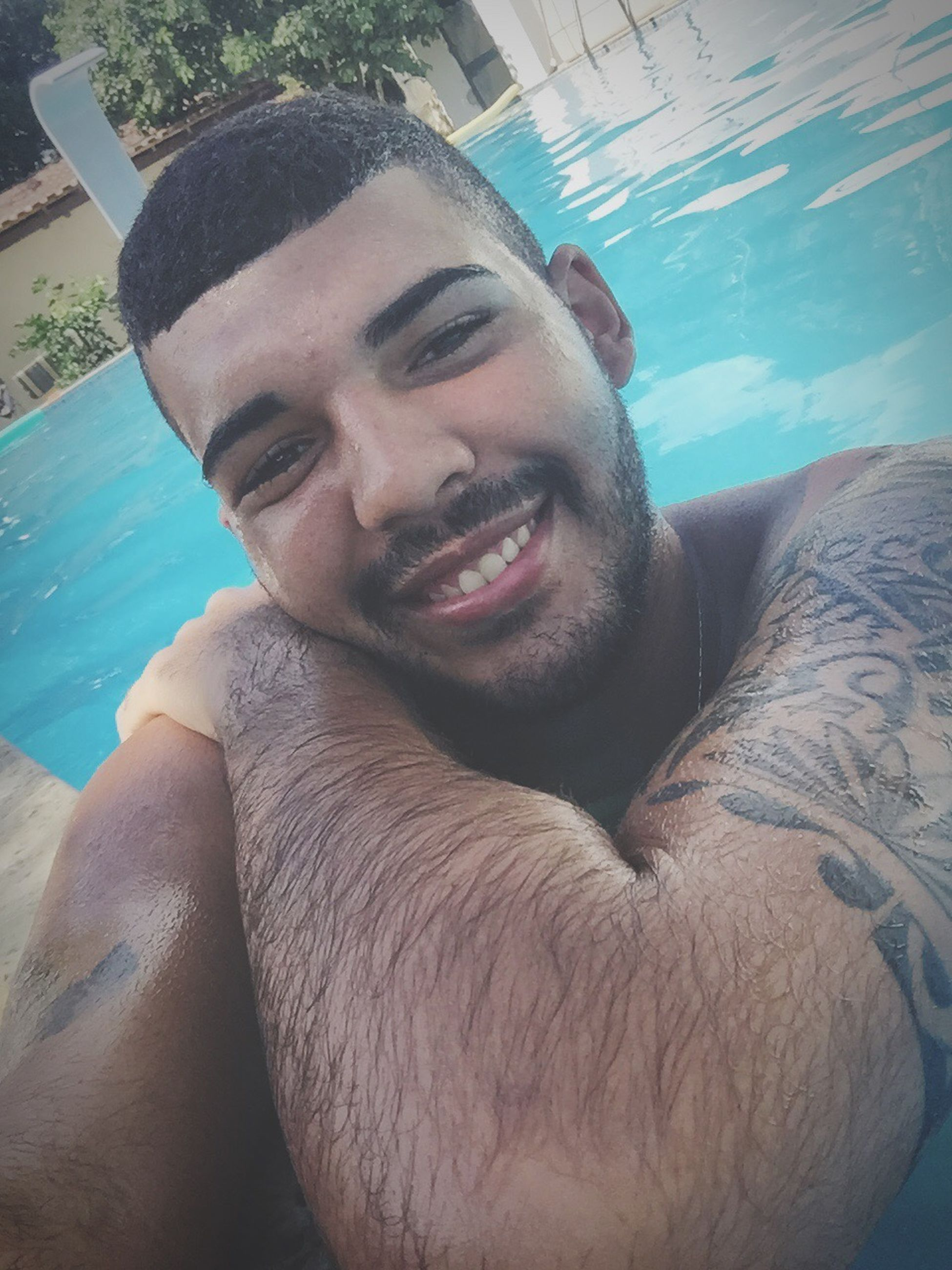 young adult, smiling, young men, males, lifestyles, cheerful, beard, swimming pool, portrait, one person, men, happiness, real people, water, adults only, outdoors, day, people, only men, one man only, close-up, adult