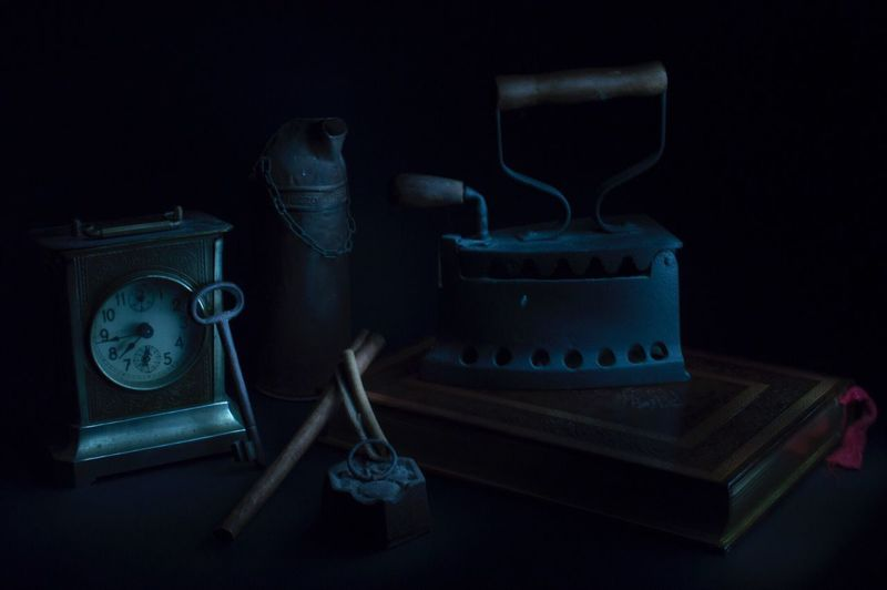 Close-up of retro iron and table clock