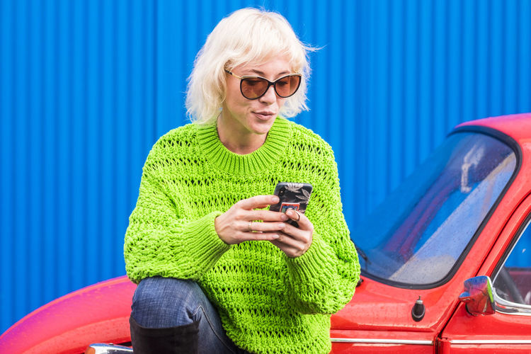 Blonde beautiful addicted girl use mobile phone outdoor sitting on a red vintage classic car. green sweater and casual jeans and blue metal wall on background - colors concept for people portrait with technology Glasses Eyeglasses  Adult One Person Technology Three Quarter Length Smiling Mobile Phone Sunglasses Happiness Wireless Technology Sitting Lifestyles Casual Clothing Communication Telephone Women Smart Phone Hairstyle Outdoors Young Woman Blond Hair Using Phone Green Color Colorful
