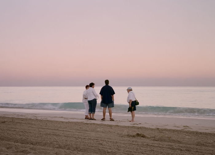 Friends walking on beach against clear sky during sunset