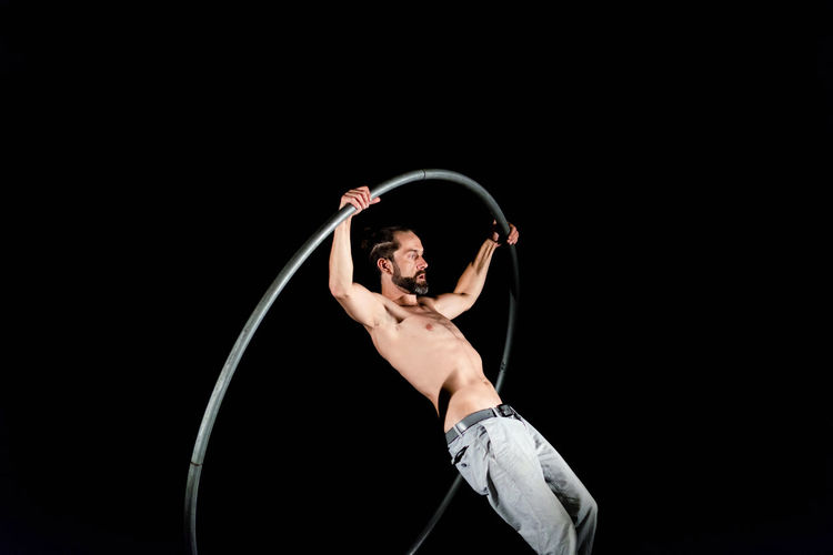 Circus Adult Arms Raised Arts Culture And Entertainment Black Background Copy Space Dancing Front View Holding Human Arm Indoors  One Person Performance Shirtless Skill  Standing Strength Studio Shot Three Quarter Length Young Adult Young Men