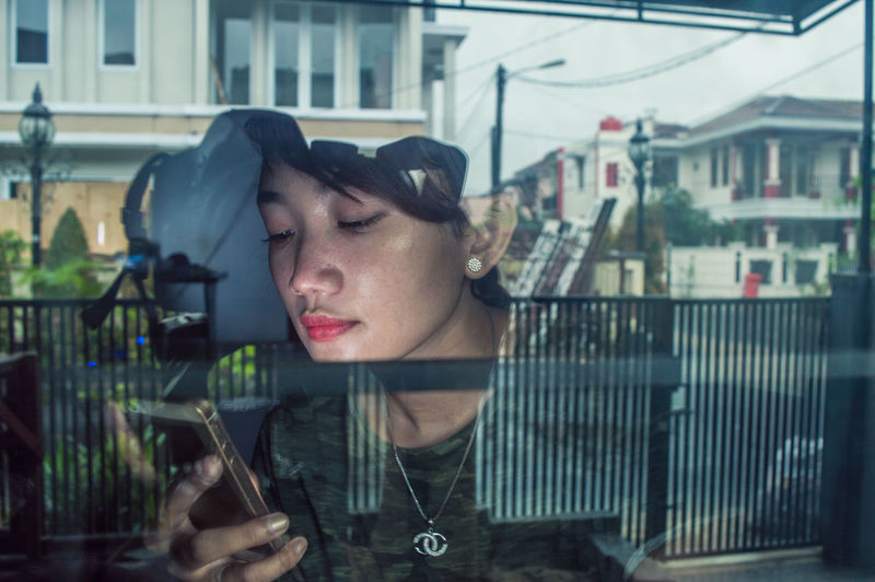 Woman using mobile phone with reflection on glass wall