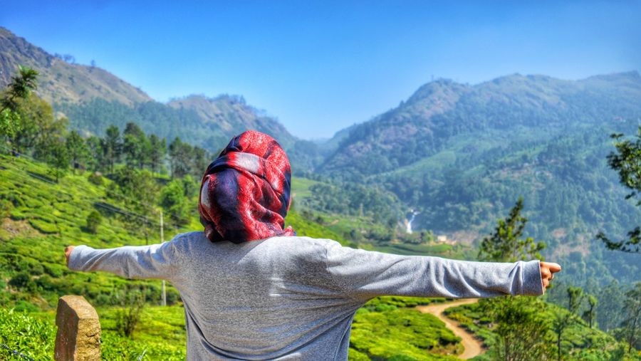 Rear View Of Woman With Arms Outstretched Standing On Mountain In Sunny Day
