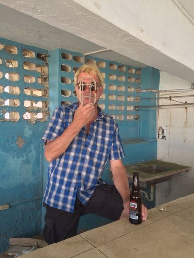 Man Holding Metal Grate In Front Of Face With Beer Bottle At Abandoned Building