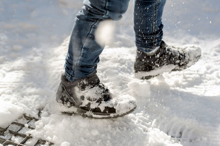 Photo of child's feet in winter boots walking in the snow.