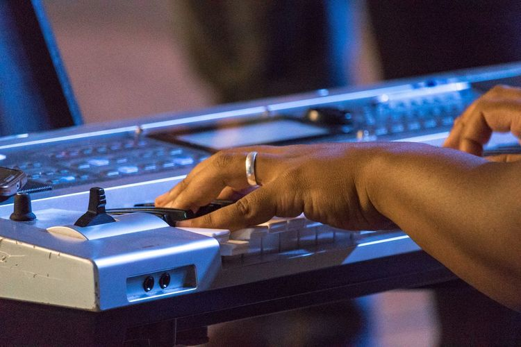Cropped hands playing synthesizer