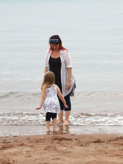 Mother and daughter standing at beach