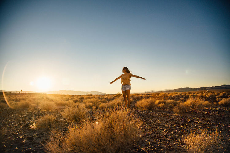 Woman With Arms Outstretched Standing On Field Against Clear Sky