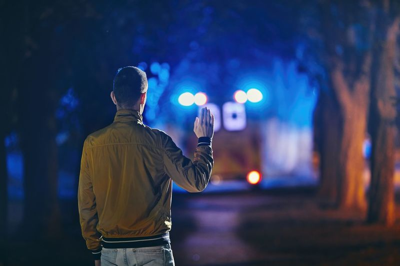 Rear view of man gesturing to ambulance while standing in forest at night