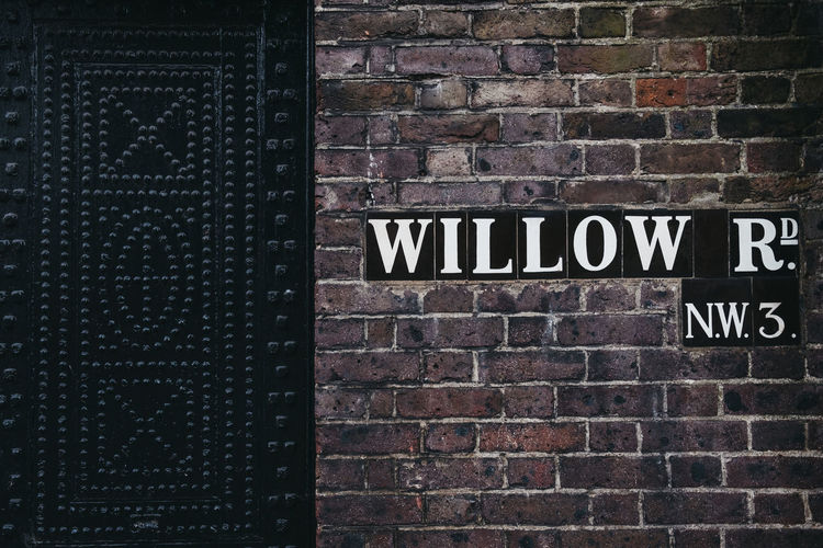 Street name sign on the Willow Road, Hampstead, London, UK. No People Western Script Wall Brick Wall Wall - Building Feature Sign Information Black Color Outdoors Close-up Day Building Exterior Street Name Sign London Hampstead Heath Nw3 Architecture Text Communication Travel Destinations City City Life Address Sign Europe