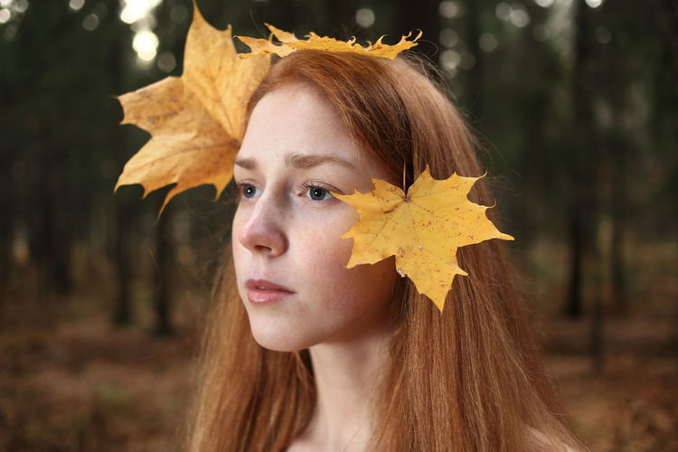 Close-up of thoughtful young woman with leaves on hair at forest during autumn