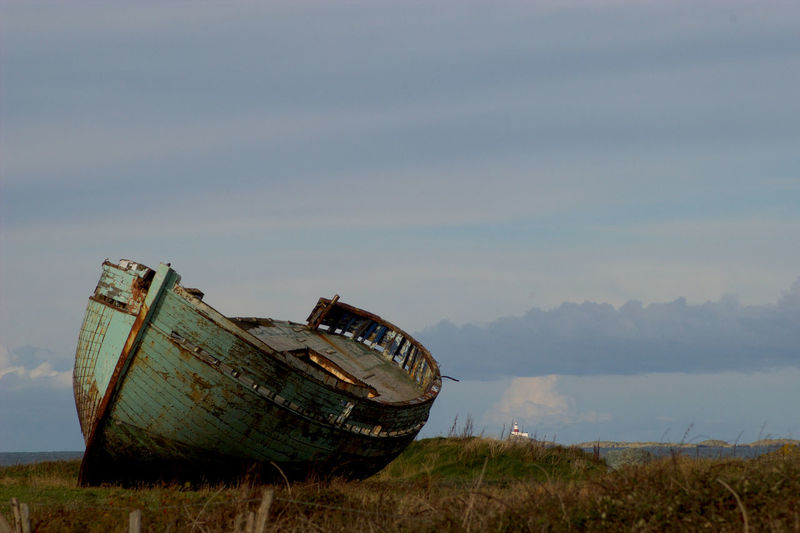 Abandoned boat on field against sky
