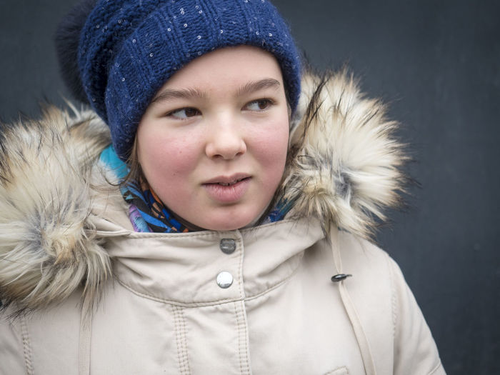Close-up of girl wearing knit hat and fur coat during winter by wall