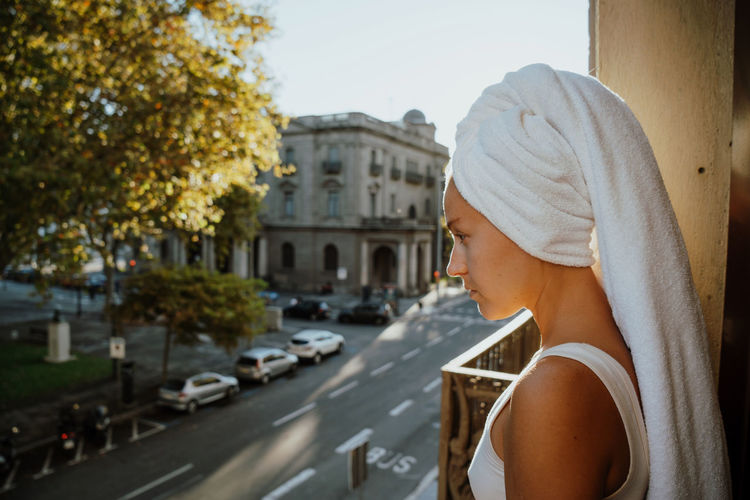 Woman standing on the balcony with bath towel