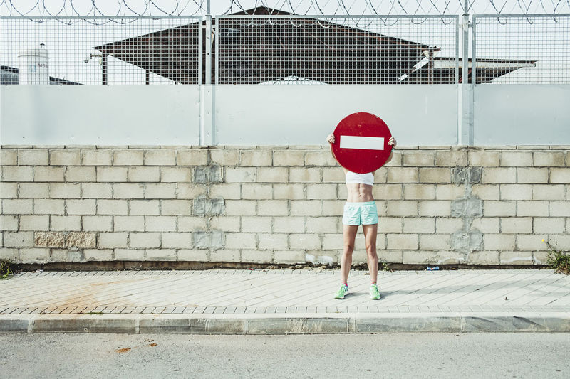 Rear view of boy standing against red wall