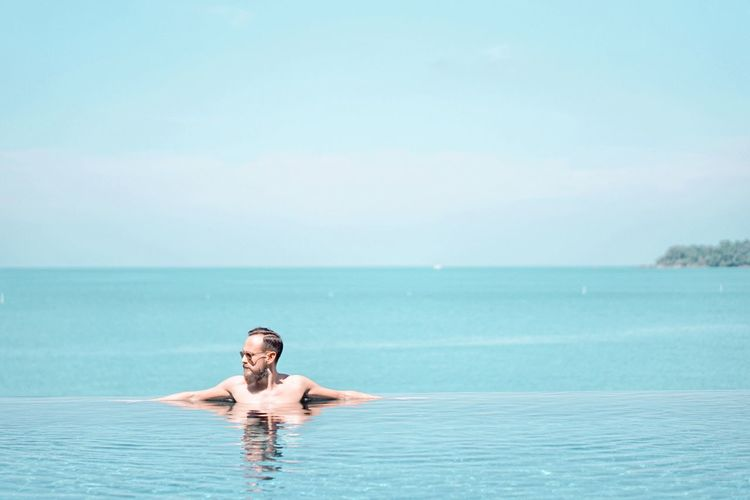 Man Swimming In Infinity Pool Against Sky