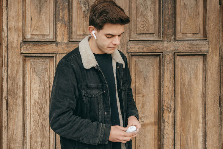 Young man using phone while standing on wood