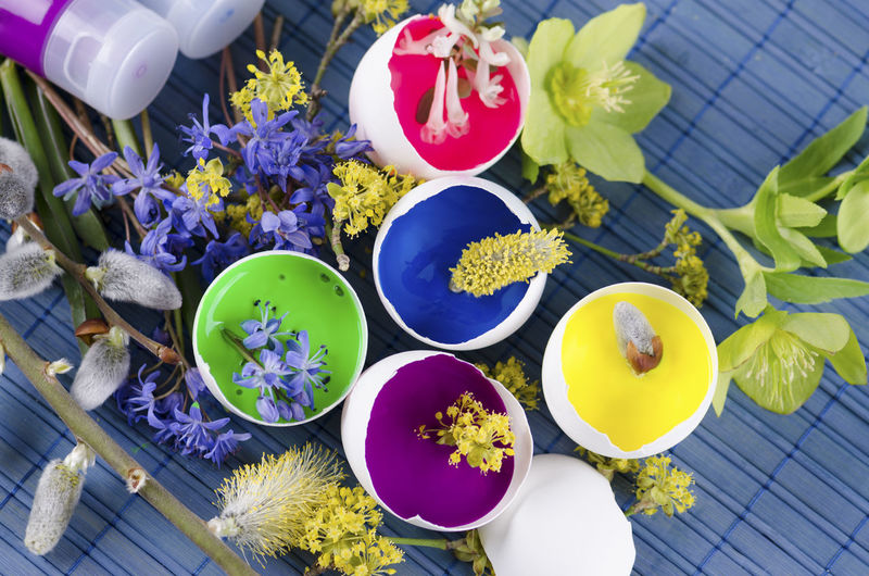 Close-up of eggshell with flowers and paint tubes on table