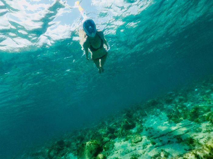 Woman Wearing Scuba Mask While Swimming In Sea