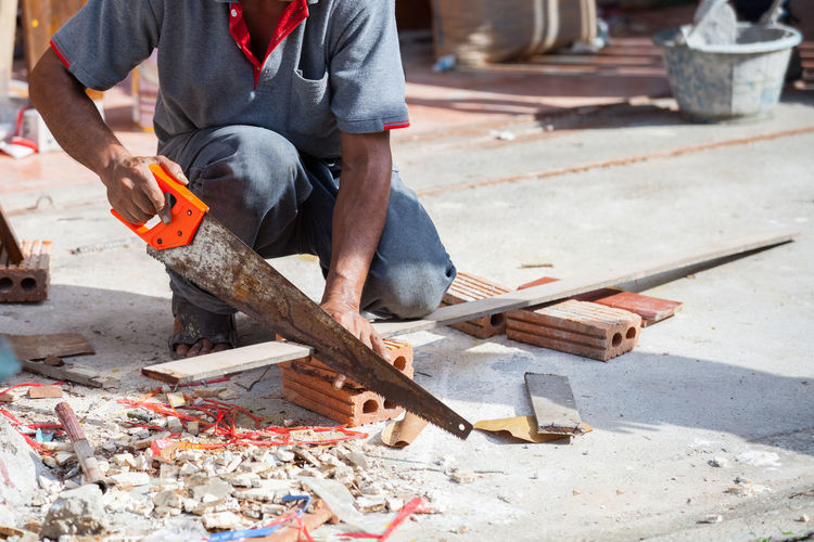 Low section of man cutting plank on floor