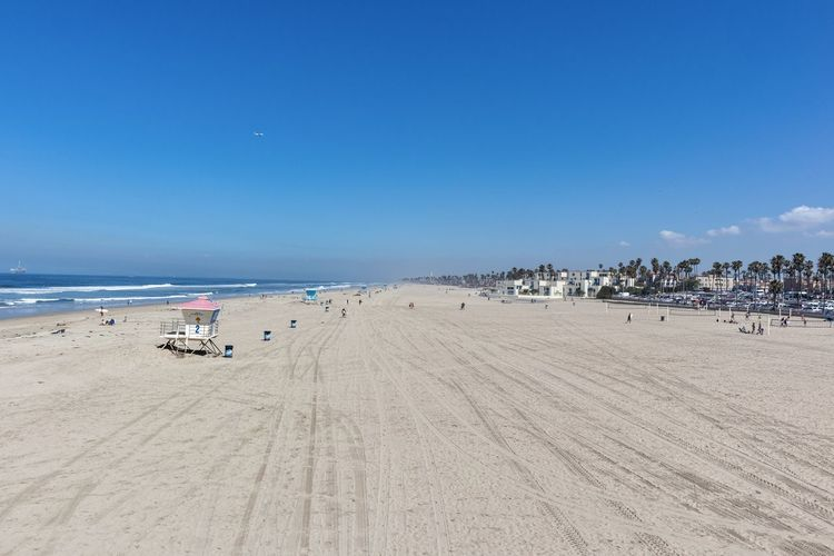 Huntington Beach coastline against blue sky Huntington Beach Orange County Southern California Beach Land Sand Sea Sky Water Scenics - Nature Incidental People Beauty In Nature Nature Copy Space Blue Tranquil Scene Horizon Tranquility Day Horizon Over Water Summer Holiday Outdoors