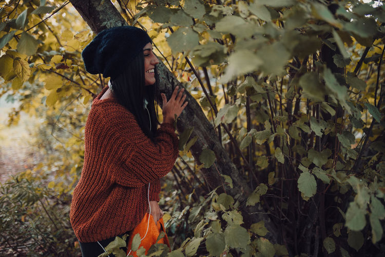 Side view of woman standing on leaves