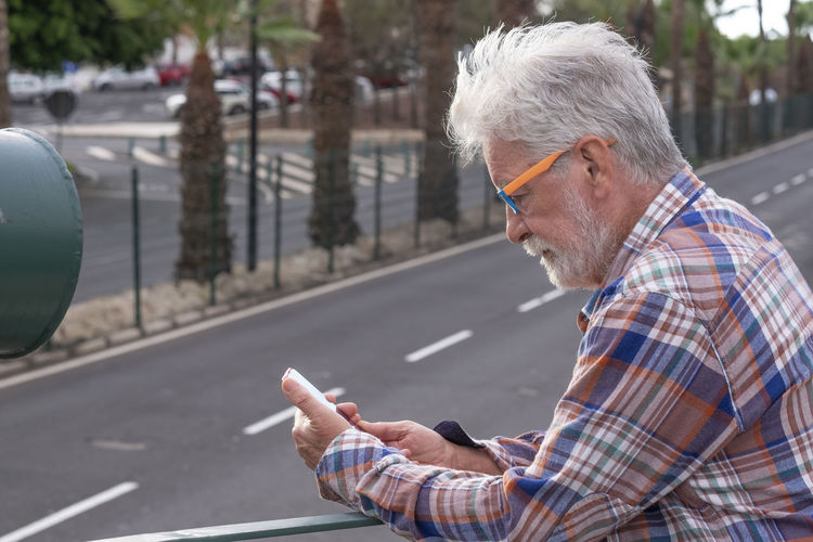 Side view of man using mobile phone on road