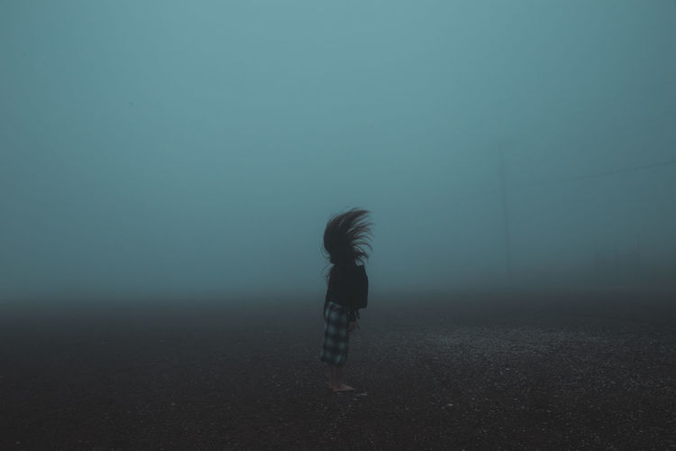 Side view of woman tossing hair while standing on field during foggy weather