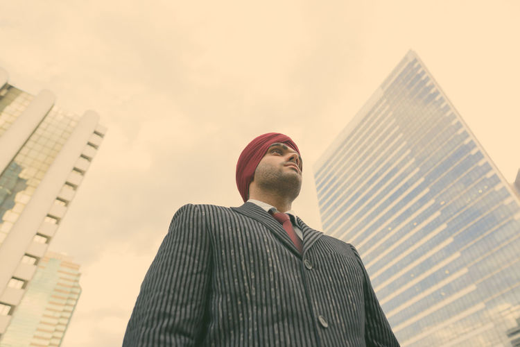 Low angle view of man looking at modern buildings against sky