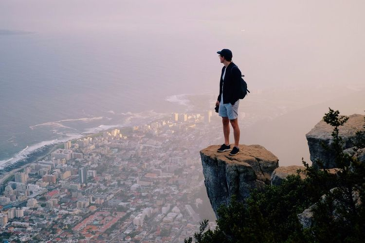 Abe Louw peering over Cape Town from Lionshead. Adventure Buddies