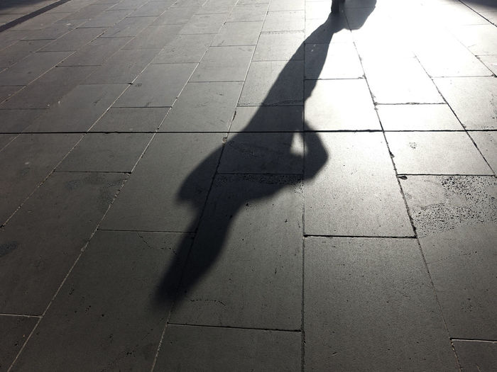 hooded figure in shadow Shadow Sunlight Real People Footpath Low Section Unrecognizable Person Street Day Focus On Shadow Human Leg Flooring City People Sidewalk Walking Outdoors Paving Stone Body Part Tiled Floor Human Limb Human Foot Hooded Stranger Dangerous Criminal