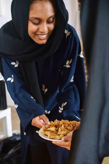 Muslim women wearing abayas gifting and sharing arabic sweets during ramadan