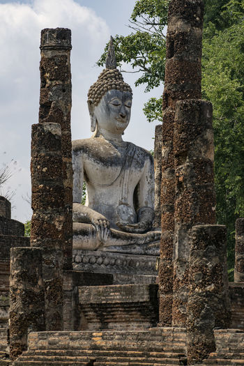 Ruined buddha statue and columns against sky