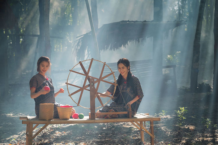 Two Beautiful Thai women smile in karen suit spinning thread on a bamboo mat in a forest nature local village Thailand Casual Clothing Day Full Length Happiness Lifestyles Looking At Camera Nature Outdoors Portrait Real People Sitting Smiling Togetherness Two People Wood - Material Young Adult Young Women