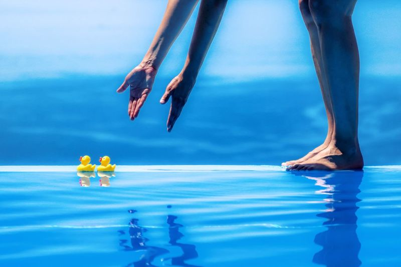 Low Section Of Standing By Swimming Pool With Rubber Ducks