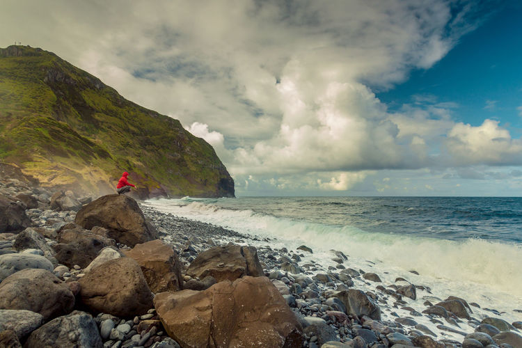 Side view of woman crouching on rock against cloudy sky