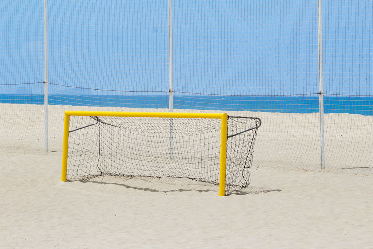 View of yellow football goal on beach against blue sky