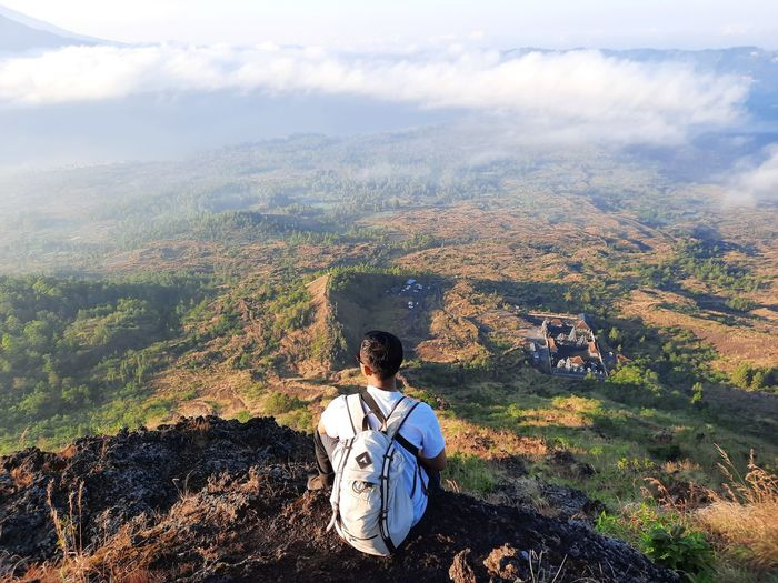 Young man looking at the view from the top of the mountain