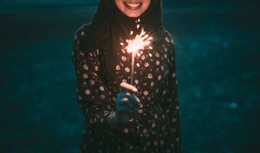 Midsection of smiling woman holding lit sparkler at night