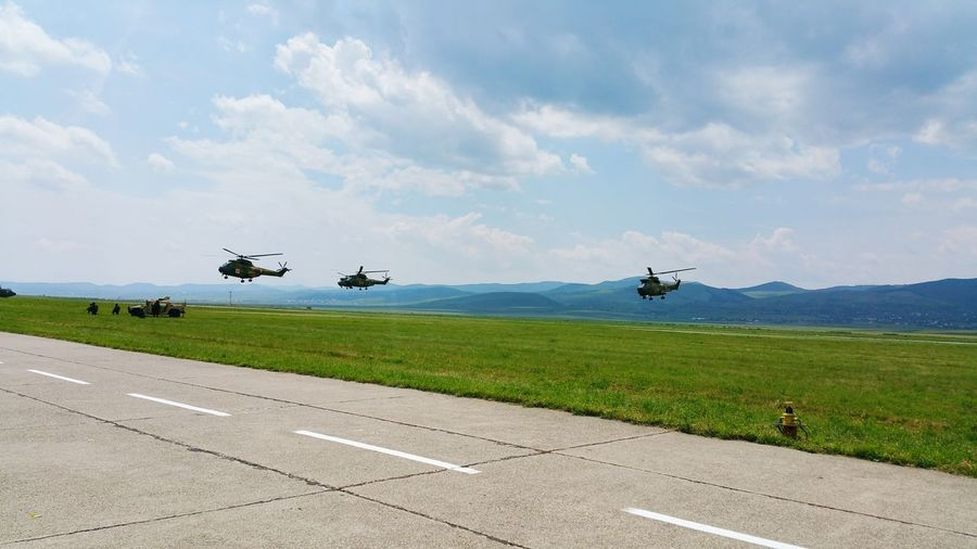 Military helicopters flying over grassy landscape