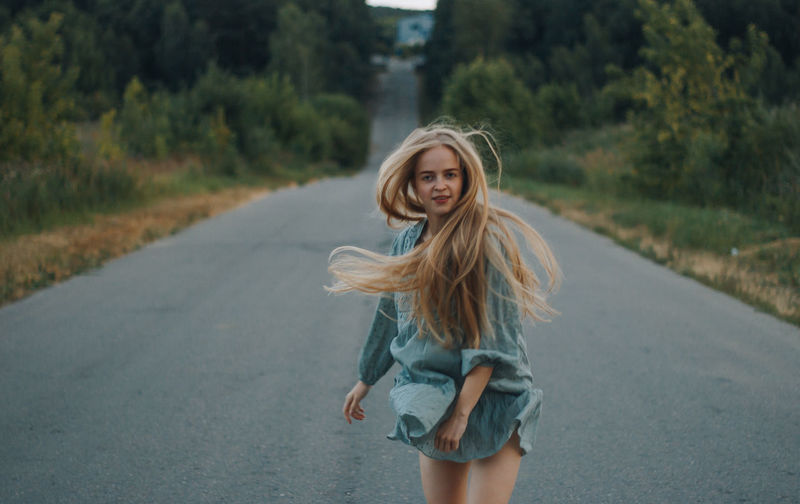 Portrait of smiling young woman on road