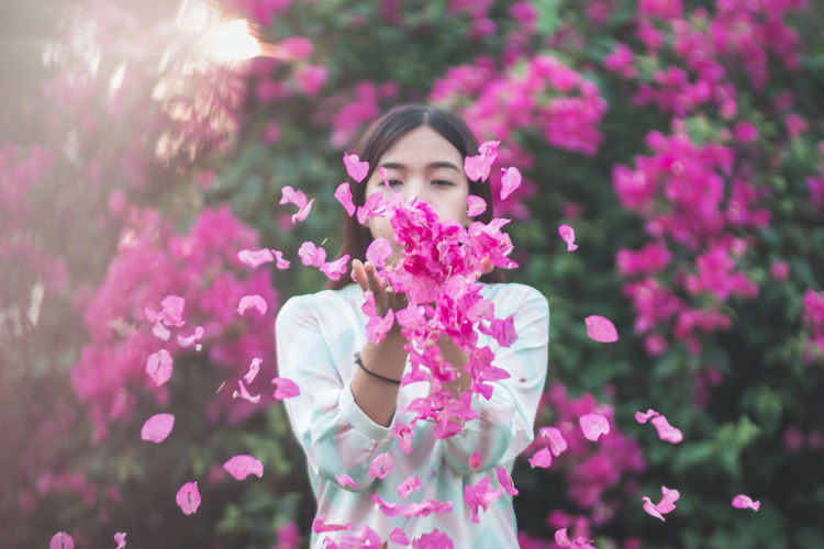 Woman throwing bougainvillea flowers