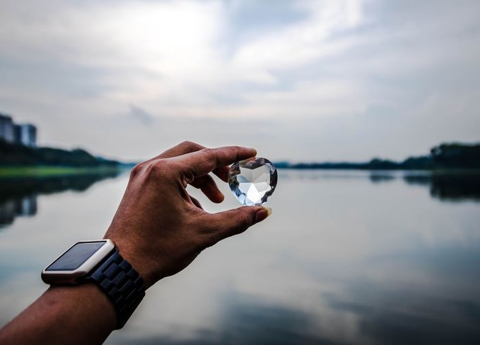 Cropped hand holding heart shape diamond by lake against cloudy sky