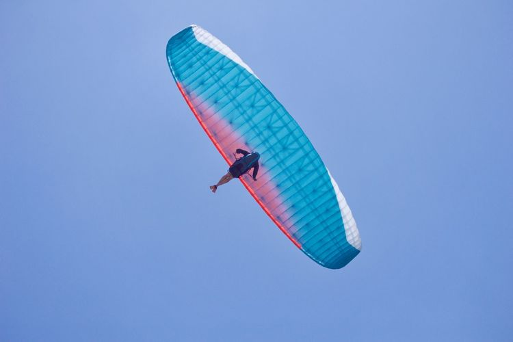 Low angle view of person kiteboarding against clear blue sky